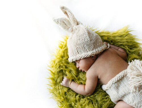 baby in white knit cap lying on green fur textile